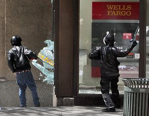 Anarchists smash the window of the Wells Fargo branch on Fourth Avenue and Seneca Street in downtown Seattle during a midday May Day march Tuesday.