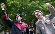 Members of the Clandestine Insurgent Rebel Clown Army take part in a midday May Day rally Tuesday at Westlake Park in Seattle.
