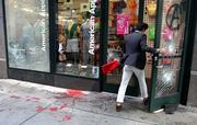 A pedestrian enters the American Apparel store on Sixth Avenue moments after the store had its windows smashed, black and red paint splattered on the storefront and a smoke bomb detonated during a midday May Day march Tuesday.