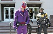 Self-described superheroes Caballero (in purple), Midnight Jack (center) and Phoenix Jones defend the old federal courthouse on Sixth Avenue in Seattle to protect the building from further damage. Moments before, anarchists smashed the glass doors, splattered black paint and let off a smoke bomb during a midday May Day march Tuesday.