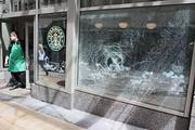 """An employee checks out the smashed window of a Starbucks store on Sixth Avenue near Pacific Place in Seattle. The window was smashed during a midday May Day """"anti-capitalism"""" march Tuesday."""