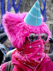 A protester in pink listens at a midday May Day rally at Westlake Park in downtown Seattle on Tuesday.