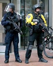 Seattle police officers stand guard outside the Wells Fargo building in downtown Seattle as a large May Day immigration march makes its way past.