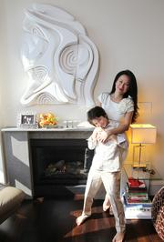 Luly Yang and her son, Lukas, in the living room of their downtown Seattle condo. The art piece hanging over the fireplace is made of stretched canvas over carved wood and was created by a neighbor of Yang's who is now a professor in Prague, Czech Republic. Yang says she loves the piece because its textures and dimensions remind her of a topographic map.