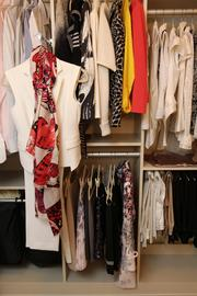 """The white cream suit on the left was designed by Luly Yang. The red, black and white scarf displayed with the suit is from Yang's """"Monarch's Tale"""" collection."""