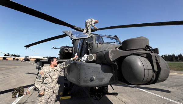 Chief Warrant Officer Aaron Adams, front, checks one of the 10 Apache helicopters just arrived at Joint Base Lewis-McChord.