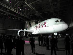 Violet lights play over the maroon-and-gray Qatar Airways 787 Dreamliner at Boeing's delivery center in Seattle.