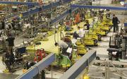 Boeing employees work on a new horizontal wing assembly system in Renton that the company says is 35 percent more efficient than the old system, in which the wings rested on their edges.