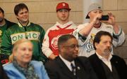 Seattle sports fans (back row, left to right) Colin Baxter, Caleb Tuohimaa and Adam Tuohimma listen intently as Seattle Mayor Mike McGinn and King County Executive Dow Constantine speak to the media and sports fans who crowded into City Hall for a press conference on Thursday (Feb. 16).