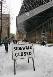 Despite a closed sign, pedestrians continue to walk along the sidewalk under the overhanging roof of the Seattle Public Library in downtown Seattle. The sidewalk was closed due to ice falling from above, but city officials were unaware of anyone being hit.