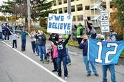 Fans cheer team buses heading to Sea-Tac Airport for the Washington Redskins game.