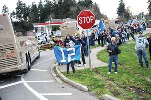 Seahawks fans line the streets as team buses head to Seattle-Tacoma International Airport en route to the Jan. 6 wild-card playoff game with the Washington Redskins.