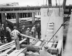 Bystanders watch as workers lower the first section of the Seattle seawall into Elliott Bay in 1934.