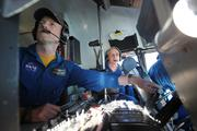 NASA flight engineers Michael Robinson (left) and Henry Taylor manage aircraft systems and assist in navigation of NASA's Super Guppy as it flies to Boeing Field in Seattle on Thursday.