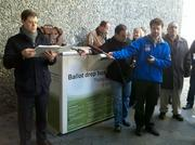 Auctioneer T.J. Parkes conducts the auction of Seattle's Smith Tower on Friday amid a media scrum.