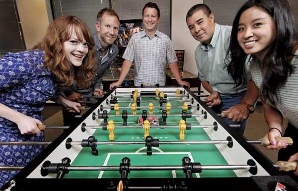 "latest twist: F5's Dan Matte (center) watches newly hired employees (left to right) Jennifer Bolton, Chris Price, Deric Villanueva and Tina Nguyen play foosball at the Seattle headquarters break room. ""A good software engineer,"" Matte says, ""loves a good challenge."""