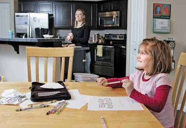 Destani Moon, 5, does homework while her mom, Jessica Moon, makes lunch in the home near Joint Base Lewis-McChord the family purchased while Jessica's husband, Army Sgt. Dustin Moon, was serving in Afghanistan.
