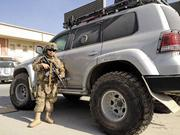 Sgt. Dustin Moon stands next to an armored Land Rover in Afghanistan, on his third tour of duty overseas.