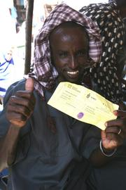A Somali refugee shows his World Concern voucher, which will allow him to purchase food from local merchants. Technology  developed by ScanMyList provides bar codes on the vouchers for more efficient tracking and distribution.