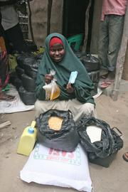 A Somali woman has food purchased from local merchants with vouchers provided by World Concern, in Dhobley, Somalia.