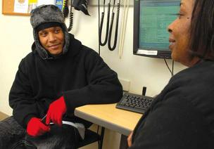 Johnathan Sutton, a patient at Seattle's Pike Market Medical Clinic, consults with Lead Medical Assistant Shelia Thomas. The clinic is part of a coalition calling for the reduction of tax breaks as a way to soften social services cuts.