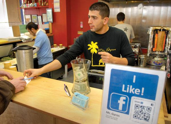 Joni Arsheed's Mr. Gyros counter includes a sign (right) with a QR code that links smartphone users to the cafe's Facebook page.