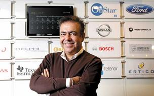 Kamyar Moinzadeh, president and CEO of Airbiquity, stands in the lobby of the company's Seattle offices, where a display shows some of the top brand names his firm has captured as customers and partners. Airbiquity, a software company, creates systems for dashboard screens that display smartphone apps and other information.