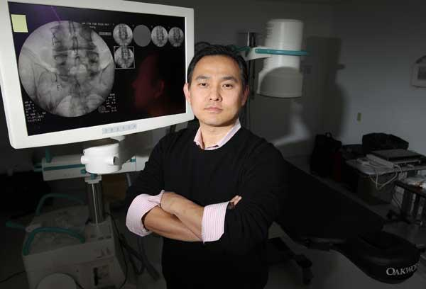 """Jae Lee, operations manager at health care provider Washington Center for Pain Management, stands next to a fluoroscope in the company's Edmonds offices. He spent last year trying to get a $3.5 million loan to purchase a building in Bellevue to expand the business. He finally succeeded after many tries but says: """"To someone trying to get a loan right now, I'd say, 'Good luck.' """""""