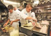 Tommy Gregorini, left, works on artichokes as Patrick Ayers takes care of halibut filets while preparing dinner at Canlis.