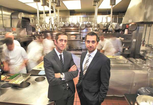 Mark Canlis, left, and his brother Brian Canlis stand in the kitchen of their flagship restaurant overlooking Lake Union.