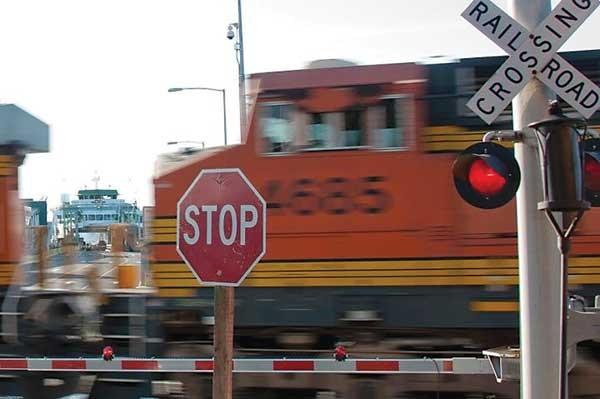 A train crosses in front of the Edmonds ferry in a rail corridor that could see more traffic if a proposed coal export terminal gets built near Bellingham.