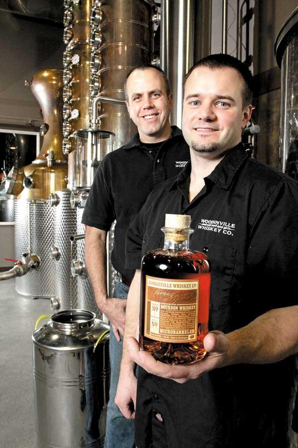 """Woodinville Whiskey's Orlin Sorensen (left) and Brett Carlile (holding a bottle of their Microbarreled Bourbon Whiskey) say changes by the state threaten their industry. """"We're looking at 30 to 50 percent more in taxes and fees per bottle,"""" Sorensen says."""