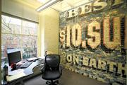 """At Discovery Bay Games' offices, now expanded to the second floor of the Buttnick Building, a wall displays old outdoor advertising for """"Best $10 Suits on Earth."""" The historic red-brick Pioneer Square neighborhood is swarming with tech creativity."""