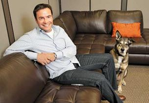 Ben Hansen, Director of The Mactus Group, with his dog Boo, hang out in the company's office lounge that is a popular gathering spot for consultants that work for the company.