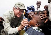 Raikes in 2011 administers polio drops to a Nigerian child during an African trip that focused on ending polio and building other immunization programs. Raikes' rural upbringing often helps him connect with the recipients of Gates Foundation programs.