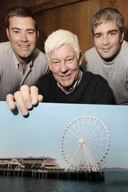 Hal Griffith, whose family has owned the Miners Landing complex on Seattle's waterfront since the 1960s, holds an artist's rendering of the 175-foot-high Seattle Great Wheel that he and his sons Kyle (left) and Troy will open at the end of June.