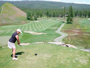 With a golfer at Rope Rider golf course's first tee, Tipple Hill, left, is a 120-foot-high pile of black coal tailings that sits in the middle of the course at Suncadia Resort near Roslyn.