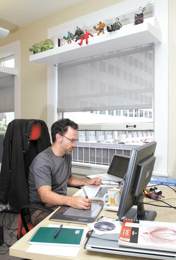 Bill McGuire, an artist with distinctdev, works at his desk in the Joseph Vance Building, whose large windows open to allow fresh air, which helps lower air conditioning costs.