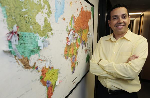 CEO Hiram Machado of Adaquest in front of a map at his company's Bellevue offices that indicates the numerous places across the globe where Adaquest employees are from. Adaquest localizes software so teams in different countries can work together.
