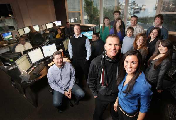 In foreground, President Chad Storey of Asset Realty, left, and Executive Director Michelle Wilson, right front, stand with their staff in the company's production center in Kirkland. Storey says the company is a Match.com for residential real estate.