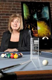 Niki McKay, principal at Blue Danube Productions, sits in the company's offices in Seattle's Pioneer Square neighborhood, where a pool table doubles as a conference table. Sitting on the pool table is an award the company won for its work on Quadstock 2011, a music festival at Seattle University.