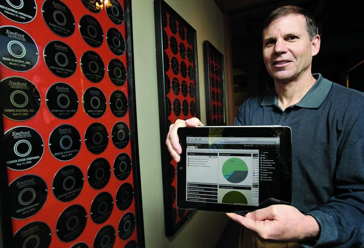 """John Chaney, co-founder of Dexter + Chaney, holds an iPad showing one of the software company's products, """"Spectrum Construction Management Software."""" He's standing beside a hallway display of CDs commemorating the firm's clients, in the firm's North Seattle office.."""