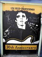 """When Lou Reed visited the Easy Street Records on Queen Anne and saw his """"Transformer"""" record cover painted on the back door of the store he signed the right door """"To Easy St. Thanks! Lou Reed."""""""