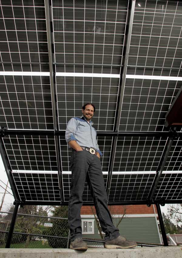 Model Remodel founder and chief executive Jason Legat is pictured under 90 solar panels at his company's Eastside Harvest House project under construction in Kirkland. This enormous bank of solar panels is one of Model Remodel's many ultra-green building techniques focused on zero-net-energy consumption homes.