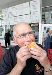 Joe Burgi, whose family owns the original Pick-Quick Drive In in Fife and is a partner in the Auburn location, bites into a classic burger at the Auburn restaurant.