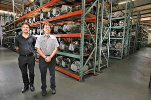 REVVED UP: Brothers and co-owners Jared DeMeerleer (left) and Ben DeMeerleer of Transmission Remanufacturing Co. stand in front of shelves of transmissions in their Kent shop. The company's revenue has increased 20 percent a year in the last two years.