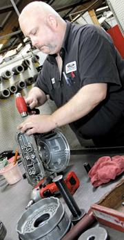 SEASONED HAND: Jeff Chapman works on an Isuzu Rodeo transmission at the Transmission Remanufacturing Co. He has worked at TRC for 16 years.