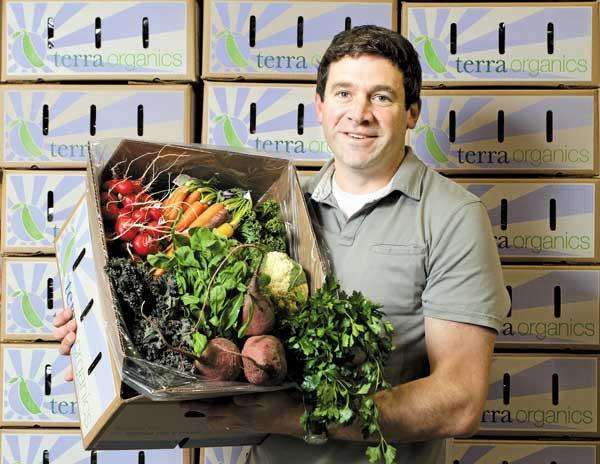 "Dan Hulse, president of Terra Organics, with a box of some of the fresh organic produce that the company delivers to about 1,000 households in the Puget Sound area. ""Terra Organics is very accommodating to people and their busy lives,"" he said."