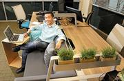 Peter Chee, CEO of Thinkspace, settles into a built-in couch in the co-working space at Thinkspace. Tenants can rent a dedicated desk for $575 a month.