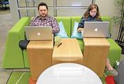 Russ Oja and Alison Ulie, of Apple Crate Marketing, work at one of  colorful couches in the co-working space at Thinkspace in Redmond.